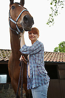Woman with horse outside stable portrait
