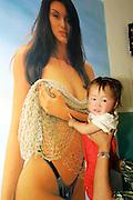 GOBI DESERT, MONGOLIA..08/31/2001.Little kid with erotic poster at a tea house, Bayangovi..(Photo by Heimo Aga).
