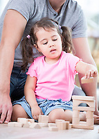 Little girl playing with wooden blocks against father in house