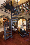Spiral staircase leading to a library in a large luxurious home. Photo by Brandon Alms Photography