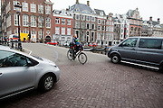 In Amsterdam rijdt een vrouw met een kindje voorop de fiets tussen twee auto's door.<br /> <br /> In Amsterdam a woman with a child on the front of the bike rides between two cars.