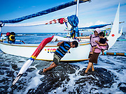 29 JULY 2017 - AIRKUNING, BALI, INDONESIA: A family lands their outrigger fishing canoe after the husband spent a night at sea, fishing in the Indian Ocean, in Airkuning, a Muslim fishing village on the southwest corner of Bali. Villagers said their regular catch of fish has been diminishing for several years, and that are some mornings that they come back to shore with having caught any fish.    PHOTO BY JACK KURTZ