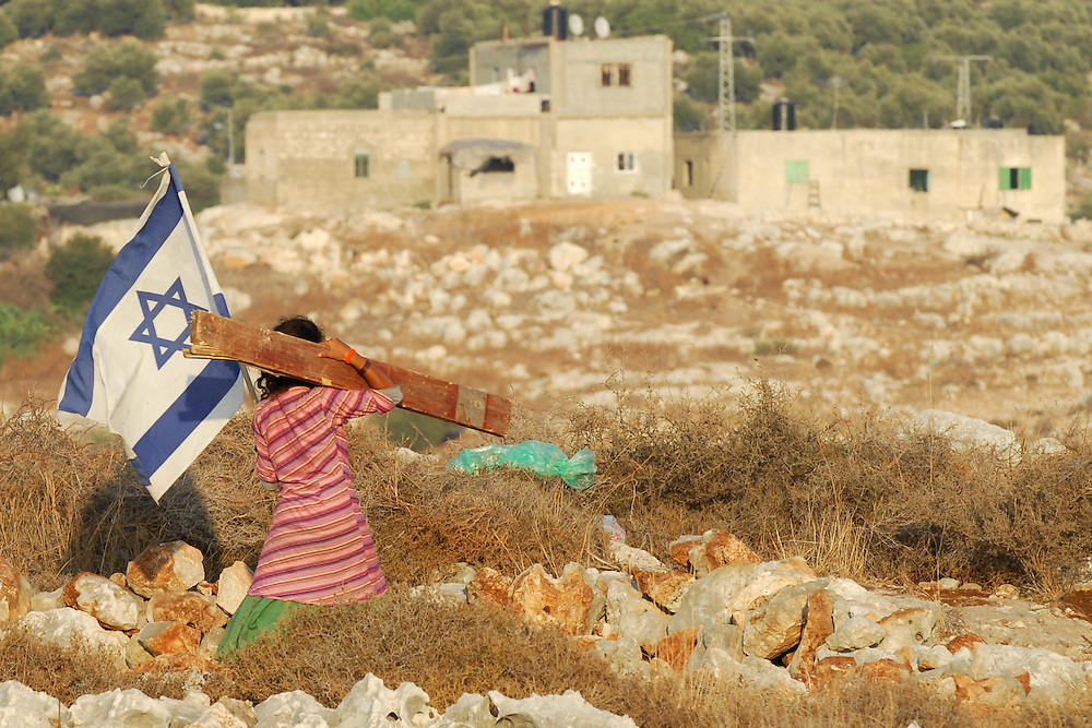 An Israeli settler girl caries an Israeli flag and a log during construction of the illegal outpost of Givat Tzuria near the Jewish settlement of Avnei Hefetz, located East of the West Bank Palestinian city of Tulkarem, July 28, 2009.