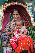 A woman sits on a rickshaw with a child on her lap outside the Central train station in Dhaka, Bangladesh.