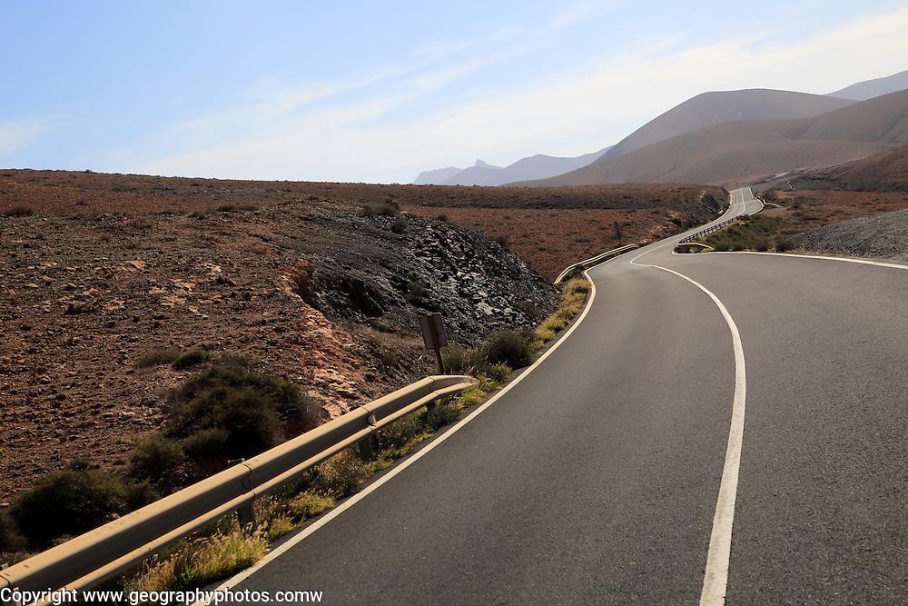 Tarmac road crossing barren desert mountainous land between Pajara and La Pared, Fuerteventura, Canary Islands, Spain