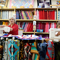 070114       Cayla Nimmo<br /> <br /> Terry Jones, left, and Marjorie Polich, right, work on the finishing touches of the &quot;Quilts of Valor&quot; at Gallup Service Mart Tuesday afternoon.