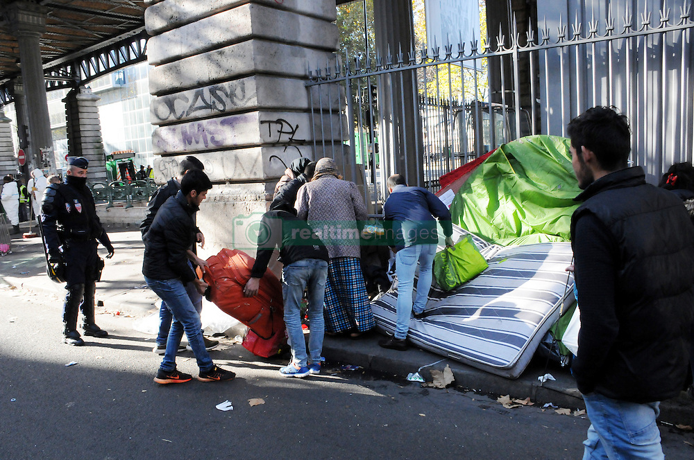 """Migrants stand in street near the Jaures and Stalingrad metro stations, in northern Paris, France, on October 31, 2016, during a police operation aiming at a future evacuation of a migrant camp. An operation of """"administrative control"""" was underway on early October 31 in the Jaures/Stalingrad quarter before a future evacuation, whose date has not yet been set, according to a police source. The makeshift camp on the outskirts of the 10th and 19th arrondissements in the north of the capital numbers today 2,500 people, according to the City of Paris. Photo by Alain Apaydin/ABACAPRESS.COM"""