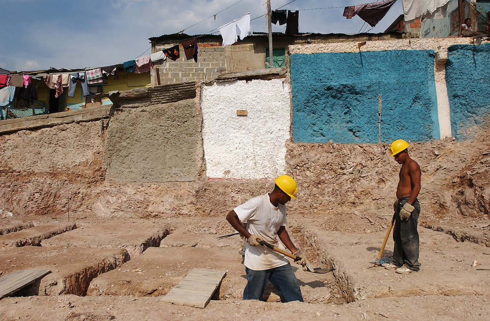 """Construction on a government project to build houses in """"El Cementerio"""", an area which has one of the many slums in Caracas.  Blanco, like all the other workers on the project, lives in the community.  Many of the houses in the community are currently made of tin and cardboard."""