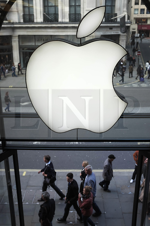 © Licensed to London News Pictures. 27/10/2013. London, UK.  High street shoppers walk beneath an Apple logo display at Apple's UK flagship Regent Street store.  Apple is to announce its Q4 Fiscal Results tomorrow.  Photo credit : Richard Isaac/LNP