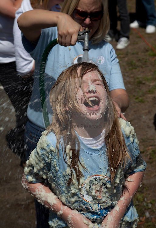 ST GEORGE, SC - APRIL 18: A young participant is hosed down after rolling around in a giant vat of grits April 18, 2009 during the World Grits Festival in St. George, SC. The event is won by the person who sticks the most grits to their body.  (Photo Richard Ellis)