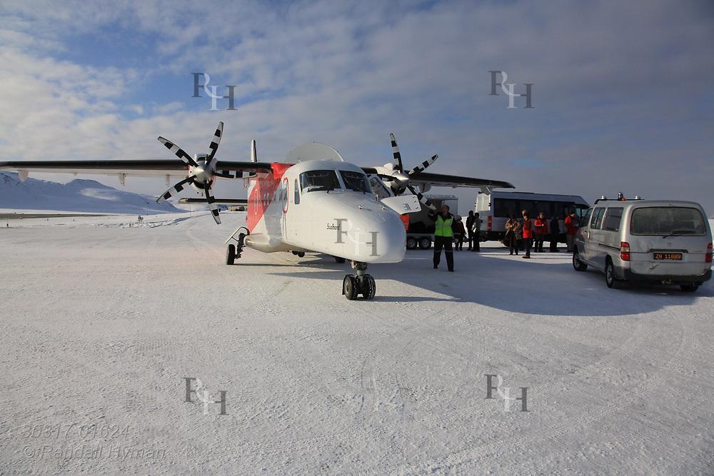 Regularly-scheduled Lufttransport Dornier Do 228 airplane unloads at the Hamnerabben Airport in Ny-Alesund on Spitsbergen island in Kongsfjorden; Svalbard, Norway.