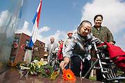 Een bewoner legt bloemen bij het monument. In verzorgingstehuis Rumah Kita in Wageningen wordt de jaarlijkse Indi&euml;-herdenking gehouden. Op 15 augustus 1945 capituleerde Japan, maar vlak daarna begon de bersiap periode in voormalig Nederlands-Indi&euml;. Met de herdenking wordt stil gestaan bij de roerige tijd, waarbij veel Indo's het land moesten verlaten.<br /> <br /> A woman is laying flowers at the monument. Residents of the nursing home for Dutch-Indonesian people Rumah Kita in Wageningen are attending a commemoration for the capitulation of Japan at the Indonesian war. After the war ended a new era started, where most of the Euro-Indonesian people had to leave the country.