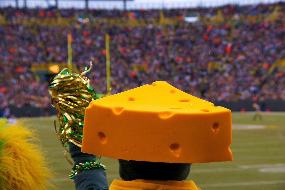 A cheesehead cheering on the Green Bay Packers at Lambeau Field.  The Green Bay Packers are one of the most historic teams in the National Football League.