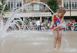 © Licensed to London News Pictures . 17/07/2013 . Nottingham, UK . Three-year-old Chloe Turner, of Long Eaton, have fun at the water spring in Market Square House, Nottingham, as the heatwave continues across the UK with temperatures soaring to 30 degrees Celsius. Photo credit : /LNP