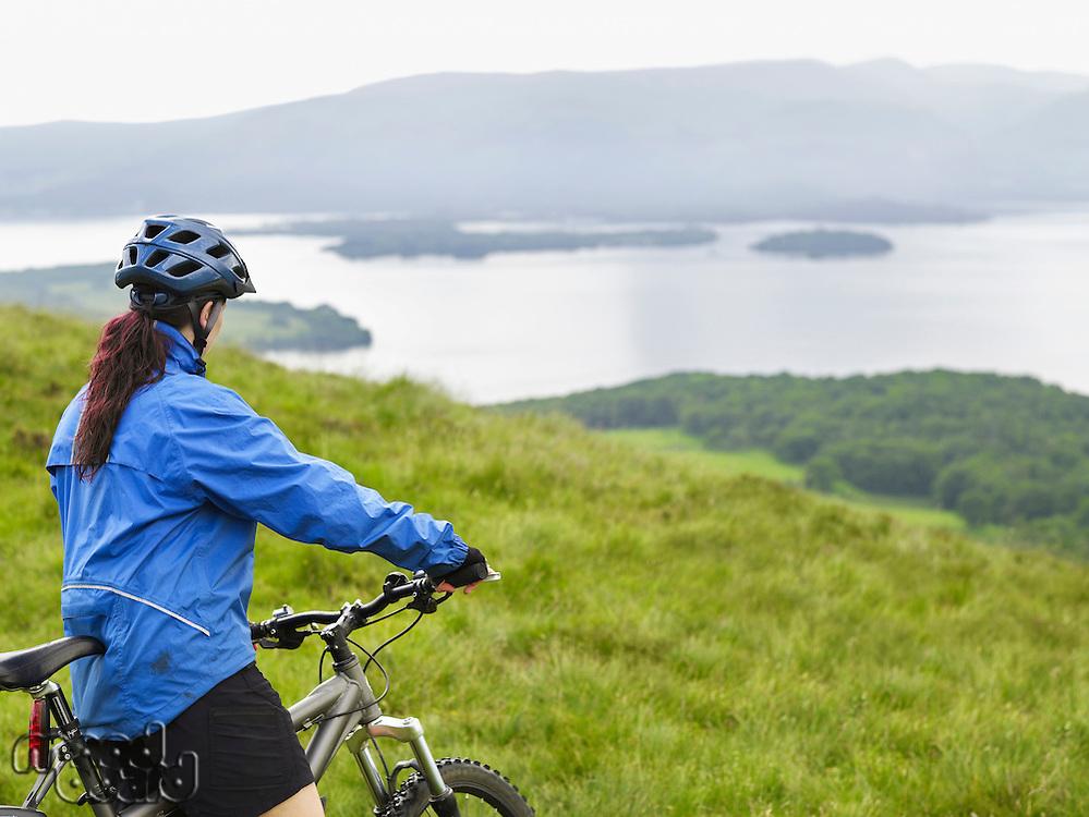 Woman on bicycle near lake