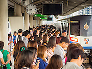 28 OCTOBER 2014 - BANGKOK, THAILAND:  Passengers going into Bangkok on the Silom line of the Bangkok Skytrain wait for an arriving train on the Saphan Taksin station platform. The Skytrain (called the BTS) system has a combined length of 36 kilometres and includes 34 stations, including Saphan Taksin. While there are two train tracks for most stretches of the Skytrain system, the portion on the Saphan Taksin Bridge spanning the Chao Phraya River has just one track due to limited space, causing a bottleneck when an outbound train and inbound train arrive at the bridge at the same time. The Bangkok Metropolitan Authority (BMA) had sought permission from the Department of Rural Roads to expand the Taksin Bridge in order to make way for an additional track, but the department had said it was not possible. The Saphan Taksin  station was originally supposed to be temporary and is one of the busiest on the system. It's a connecting station for the Chao Phraya River boats used by Thai commuters coming into the city from neighboring provinces and tourists who use the boats to go upriver into the old parts of Bangkok from the central business district. More than 4,000 commuters a day use the station. The BMA plans to build an elevated moving sidewalk to the river from Surasak BTS station about one kilometer away. Surasak is the nearest station to Saphan Taksin. The Skytrain system has a combined length of 36 kilometres and includes 34 stations, including Saphan Taksin.       PHOTO BY JACK KURTZ