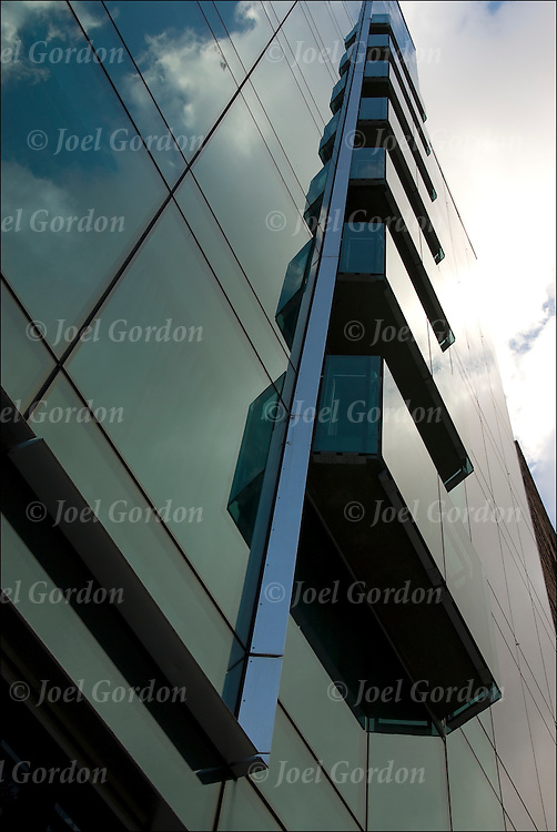Graphic perspective looking up, sky and clouds reflected off steel and glass exterior architectural exterior of modern building on 7th Avenue and 19th Street.