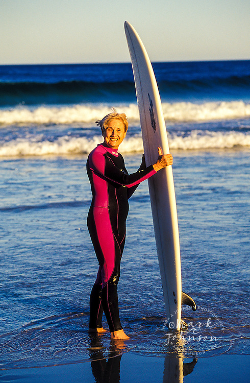 Mature woman surfer at beach, Queensland, Australia