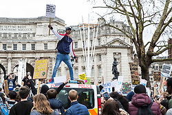London, UK. 15th March, 2019. A student climbs on top of a police vehicle as thousands of students take part in the second Youth Strike 4 Climate. After gathering in Parliament Square, students marched to Buckingham Palace and then joined a protest by Extinction Rebellion which blocked Westminster Bridge. The strike was organised by UK Student Climate Network and the UK Youth Climate Coalition to demand that the Government declare a climate emergency and take positive steps to address the climate crisis, including highlighting the issue as part of the school curriculum, as well as lowering the voting age to 16, and similar events were held around the world.