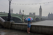 A lone wet tourist stands overlooking the River Thames from London's Southbank, enduring heavy summer rainfall in the capital.