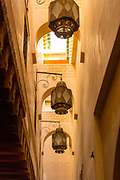 FEZ, MOROCCO - 1ST FEBRUARY 2018 - Streets and alleyways in the old Medina District of Fez connecting to the Al-Karaouine Mosque and University complex. <br /> <br /> Established at the very beginnings of Morocco's oldest imperial city, the University of Al-Karaouine (also written as Al-Quaraouiyine and Al-Qarawiyyin) was founded in 859 and is considered by Unesco and the Guinness Book of World Records to be the oldest continually operating university in the world.<br /> <br /> From ground level, the true shape and structure of the complex is hidden, where buildings are stacked so close together that roofs touch and crossover above the alleyways. But the trail of grand doorways and wooden walls help visitors define its outline.