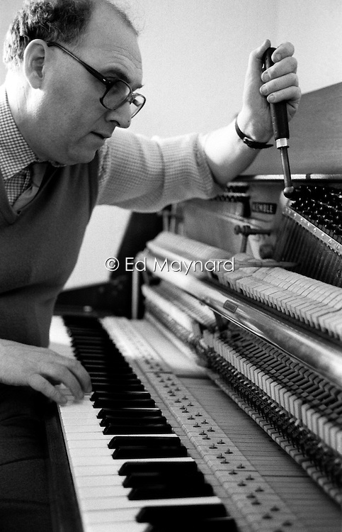 Partially sighted Paul Chrimes, a member of the Association of Blind Piano Tuners, working on a clients piano, Dudley, England, UK.