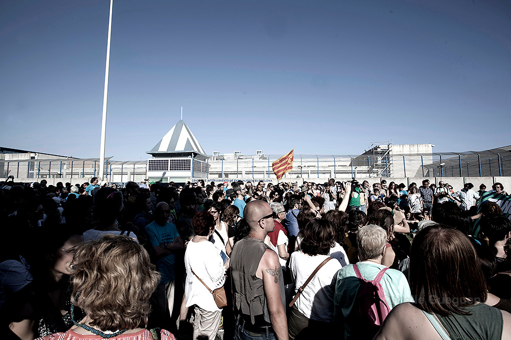 "A crowd of people stand in front of the CIE entrance in support of the protest organized by""Tancarem el CIE"" to get to government to close the Immigration detention center permanently.   Barcelona 20/06/2015"