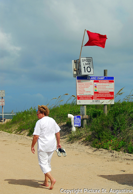 Red Flag Warning! A woman walks down the Vilano Beach Ramp in St. Augustine, Florida. The red flag signifies extreme danger for those choosing to enter the waters of the Atlantic Ocean. There are four different colored flags each indicating different beach conditions. A purple flag warns of Dangerous Marine Life, the red flag is Extreme Danger stay out of the water, a yellow flag means caution swim near a lifeguard, and the green flag is the flag for favorable conditions.