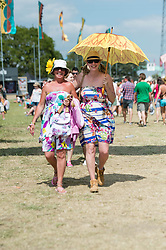 © Licensed to London News Pictures. 13/06/2014. Isle of Wight, UK.   Two women shelter from the hot sun under an umbrella during the hottest day of the year at Isle of Wight Festival 2014. Atmosphere at Isle of Wight Festival 2014.   The Isle of Wight festival is an annual music festival that takes place on the Isle of Wight. Photo credit : Richard Isaac/LNP