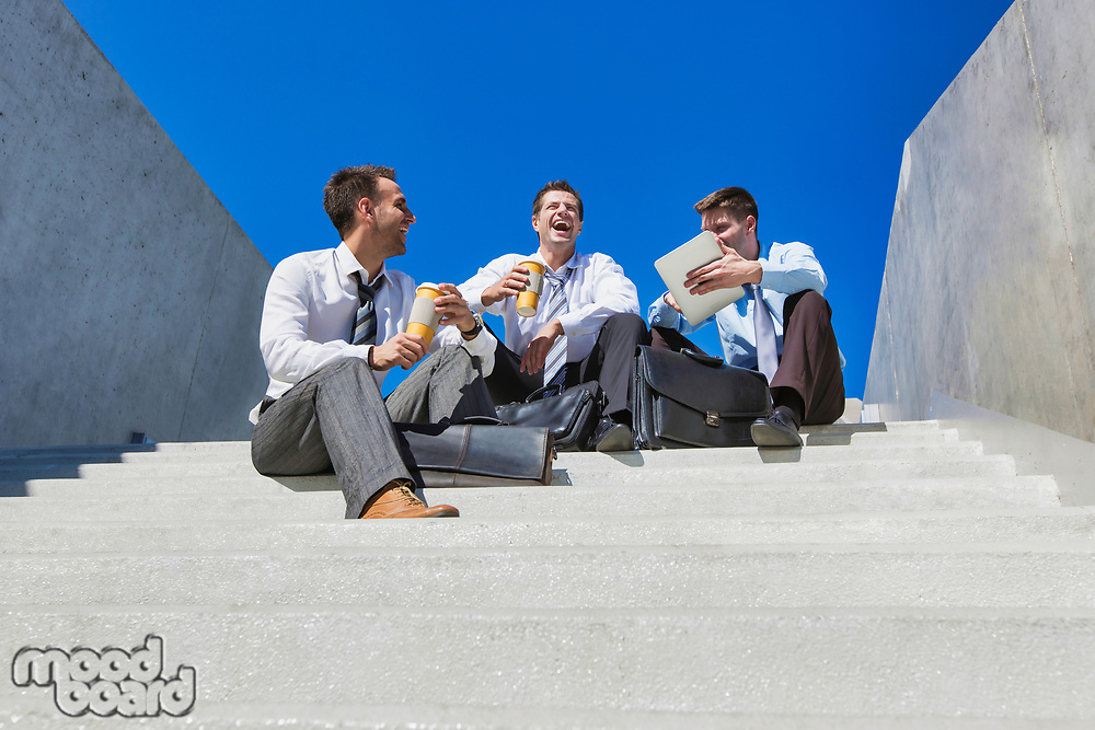Group of handsome businessman sitting on stairs while talking during break