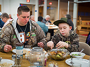 """26 FEBRUARY 2020 - FARMINGTON, MINNESOTA: ASHLEY FOLVEN and her nephew, JACOB FOLVEN eat their dinners at the community dinner at Faith Church, a United Methodist Church in Farmington, MN, about 30 minutes south of the Twin Cities. The dinner is sponsored by Loaves & Fishes, a Christian organization that provides food for community dinners and foodbanks. Farmington, with a population of 21,000, is a farming community that has become a Twin Cities suburb. The city lost its only grocery store, a Family Fresh Market, in December, 2019. The closing turned the town into a """"food desert."""" In January, Faith Church started serving the weekly meals as a response to the store's closing. About 125 people per week attend the meal at the church, which is just a few blocks from the closed grocery store. The USDA defines food deserts as having at least 33% or 500 people of a census tract's population in an urban area living 1 mile from a large grocery store or supermarket. Grocery chains Hy-Vee and Aldi both own land in Farmington but they have not said when they plan to build or open stores in the town.      PHOTO BY JACK KURTZ"""