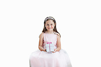 Portrait of cute girl holding gift box over white background