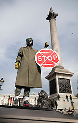 © Licensed to London News Pictures. 07/10/2019. London, UK. An Extinction Rebellion activist in a gas mask stands on a car in Trafalgar Square, central London. Activists are converging on Westminster blockading roads in the area for at least two weeks calling on government departments to 'Tell the Truth' about what they are doing to tackle the Emergency. Photo credit: Peter Macdiarmid/LNP
