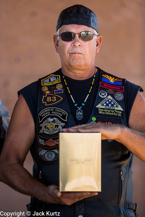 08 OCTOBER 2013 - PHOENIX, AZ: A member of Patriot Guard Riders honor guard unit holds an urn containing the cremated remains of a US military veteran. The cremated remains of 36 unclaimed US military veterans were interred at the National Memorial Cemetery in Phoenix. Members of the US military and several hundred veterans of the US military attended the service, which was a part of the Missing In America Project (MIAP).     PHOTO BY JACK KURTZ