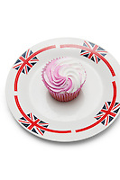 Delicious raspberry cupcake in plate over white background