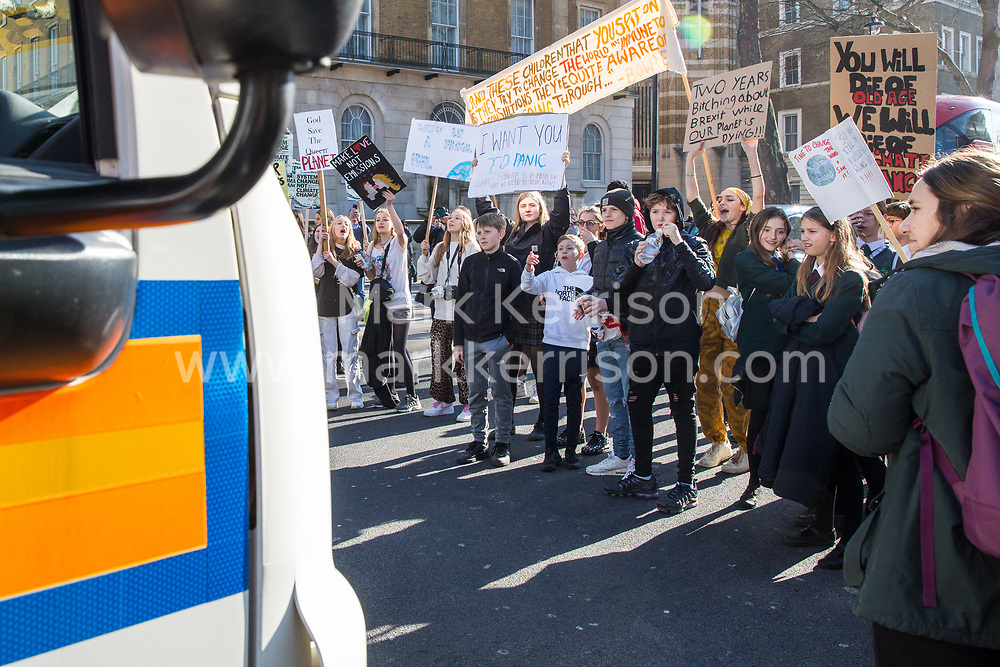 London, UK. 15th February, 2019. Students block Whitehall in front of a police vehicle during the YouthStrike4Climate for Climate Day which was attended by thousands of young people. Strike events involving schools all over the UK were organised by UK Student Climate Network and the UK Youth Climate Coalition to demand that the Government declare a climate emergency and take positive steps to address the climate crisis, including highlighting the issue as part of the school curriculum, as well as lowering the voting age to 16.