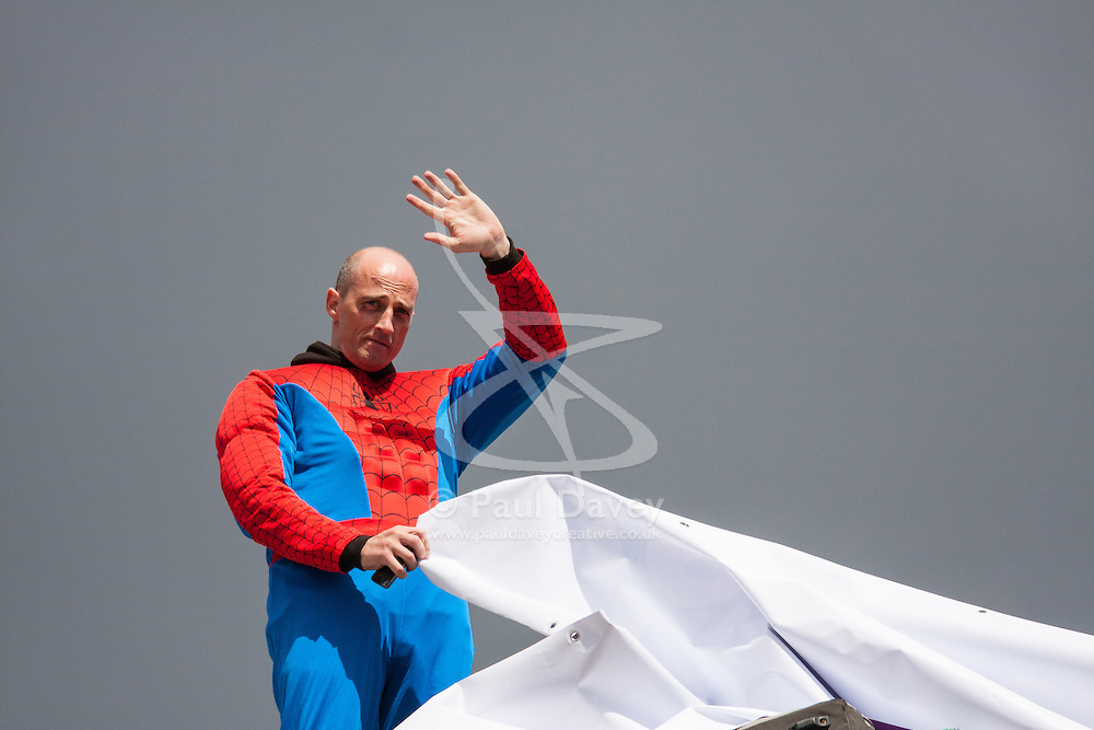 London, August 12th 2014. A Protester dressed as superhero Spiderman from Fathers For Justice hangs a banner from atop Decimus Burton's Ionic screen entrance to Hyde Park adjacent to Apsley House at  Hyde Park Corner.