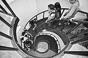 the downward spiral, people descend a stair well.