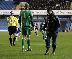 A member of the ground staff attempts to walk off with a bottle that was thrown on to the pitch  by angry fans but Referee Lee Probert spots it and wants the bottle - Photo mandatory by-line: Robin White/JMP - Tel: Mobile: 07966 386802 28/01/2014 - SPORT - FOOTBALL - The Den - Millwall - Millwall v Sheffield Wednesday - Sky Bet Championship