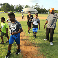 """Charles Gardner, with Real Men Stand Up, gets a kickball game organized with area boys during the 2nd annual """"Father Son Fun Day"""" at Theron Nichols Park Thursday night in Tupelo. The Family Resource Center, Tupelo Police Athletic League and Real Men Stand Up, partnered to host the event."""