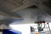 "During the turnround of the British Airways jet aircraft, a refueller checks the safety of heavy fuel nozzles that connect from his bowser truck on the apron at Heathrow Airport's Terminal 5. He is ensuring the correct plugging of the connections as some 109 tons of Jet A1 aviation fuel flow at a rate of 3,000 litres a minute which is being uplifted into the wing tanks of this Boeing 747-300, a typical quantity of extra fuel for this aeroplane bound for Los Angeles. From writer Alain de Botton's book project ""A Week at the Airport: A Heathrow Diary"" (2009). ."