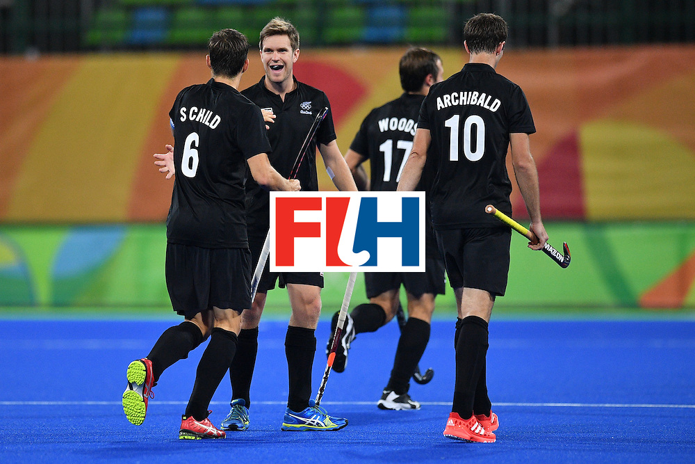 New Zealand's Simon Child (L) celebrates scoring with his teammates during the mens's field hockey Belgium vs New Zealand match of the Rio 2016 Olympics Games at the Olympic Hockey Centre in Rio de Janeiro on August, 12 2016. / AFP / Carl DE SOUZA        (Photo credit should read CARL DE SOUZA/AFP/Getty Images)