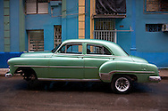 Old green American car in front of a blue building in Havana Centro, Cuba.