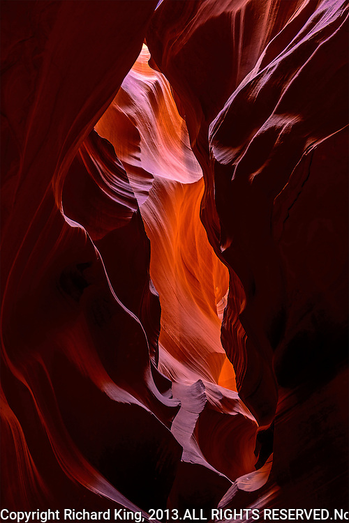 Color photograph inside the slot canyons of Page, AZ. Showing the vivid reds, oranges and purples of the rock face.