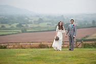 Bride and groom standing in a field with a misty view towards Seaton. Photographed at Cranberries Hideaway.