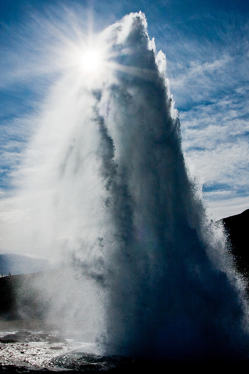 The sun peeks from behind the Strokkur Geyser. Strokkur erupts every 7 minutes or so, and is located in a place called Geysir, which gave the name to these fenomena