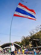 "30 DECEMBER 2013 - BANGKOK, THAILAND: An anti-government protestor waves a Thai flag at the protestors' base at Democracy Monument. Violence around the anti-government protest sites has escalated in recent days and several protestors have been hurt by small explosive devices thrown at their guard posts. As a result, protestors are fortifying their positions with sandbags and bunkers. Suthep Thaugsuban, the leader of the anti-government protests in Bangkok, has called for a new series of massive protests after the 1st of the year and said it the shutdown, or what he described was the seizure of the capital, would be the day when ""People's Revolution"" would ""begin to end and uproot the Thaksin regime.""          PHOTO BY JACK KURTZ"