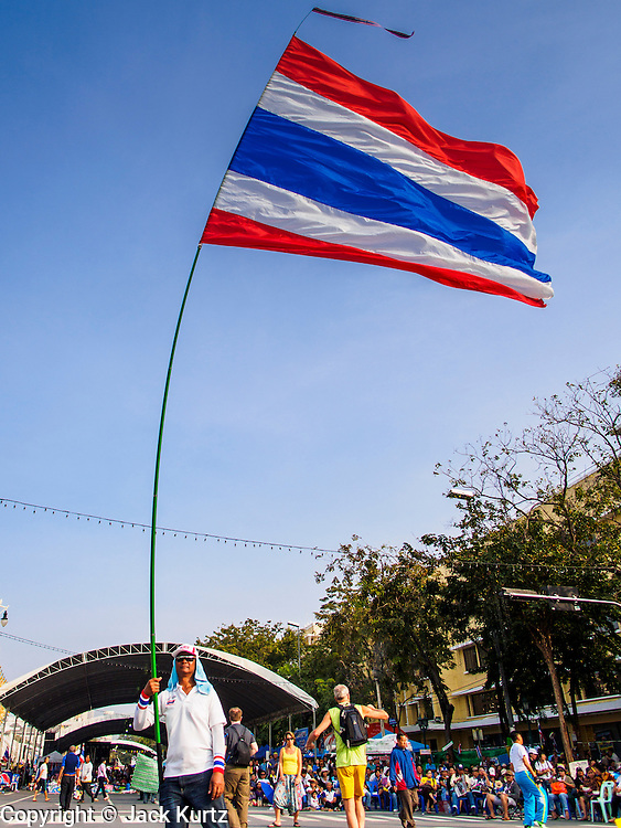 """30 DECEMBER 2013 - BANGKOK, THAILAND: An anti-government protestor waves a Thai flag at the protestors' base at Democracy Monument. Violence around the anti-government protest sites has escalated in recent days and several protestors have been hurt by small explosive devices thrown at their guard posts. As a result, protestors are fortifying their positions with sandbags and bunkers. Suthep Thaugsuban, the leader of the anti-government protests in Bangkok, has called for a new series of massive protests after the 1st of the year and said it the shutdown, or what he described was the seizure of the capital, would be the day when """"People's Revolution"""" would """"begin to end and uproot the Thaksin regime.""""          PHOTO BY JACK KURTZ"""