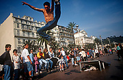 A 1990s Cote d'Azur skater performs a high stunt leap in front of a crowd of admirers on the Promenade de Anglais, on 10th May 1996, in Nice, France. (Photo by Richard Baker / In Pictures via Getty Images)