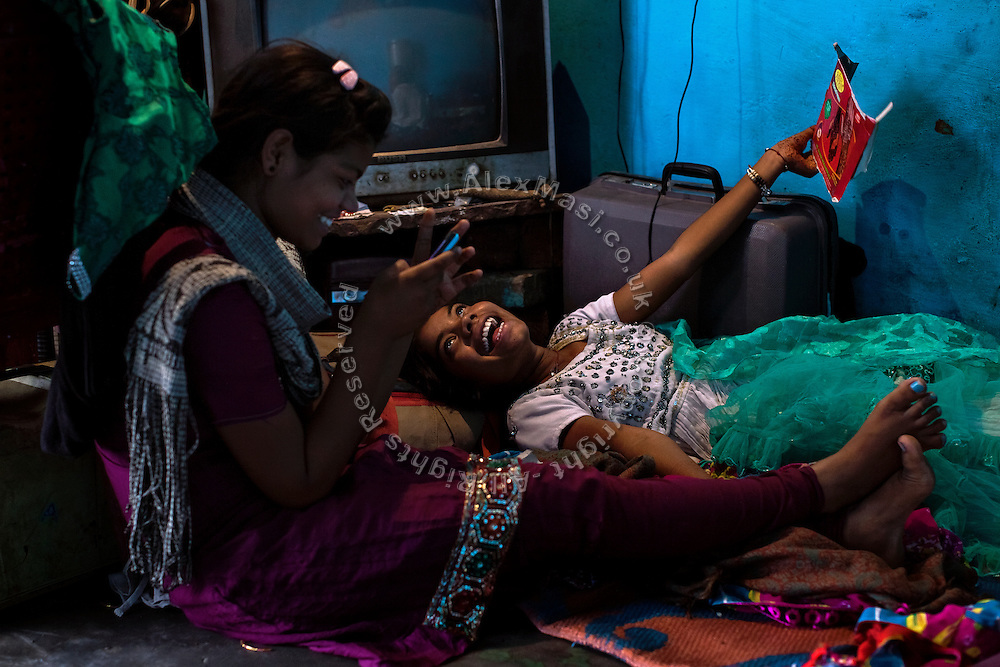 Poonam, 13, (left) is playing a game on the family's mobile phone while her older sister Jyoti, 14, is playing with a carton box on the floor of their newly built home in Oriya Basti, one of the water-contaminated colonies in Bhopal, central India, near the abandoned Union Carbide (now DOW Chemical) industrial complex, site of the infamous '1984 Gas Disaster'.